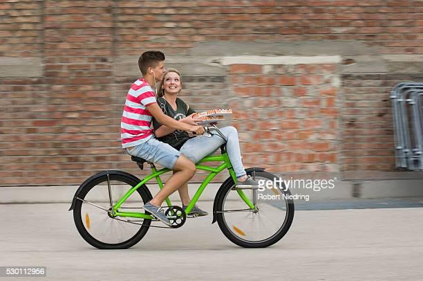 Teenage girl and teenage boy cycling