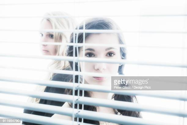 Teenage Girl And Young Blond Woman Looking Through The Blinds On A Window