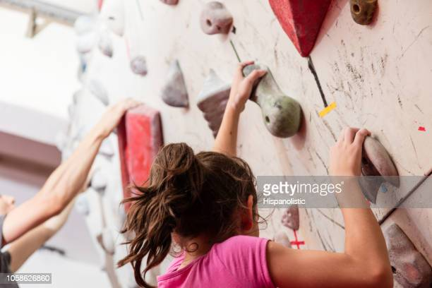 teenage girl and young man climbing an indoor wall - leisure activity stock pictures, royalty-free photos & images