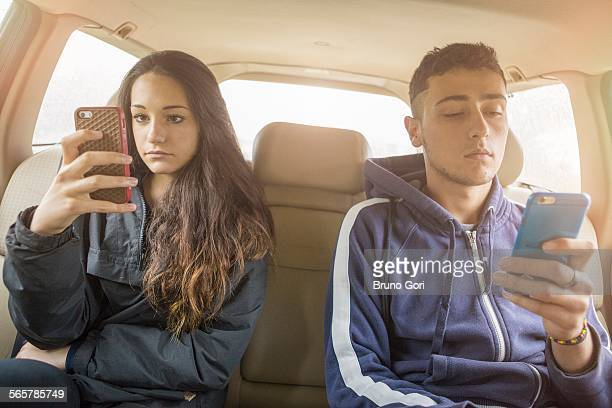 Teenage girl and young man reading separate smartphone texts in car back seat