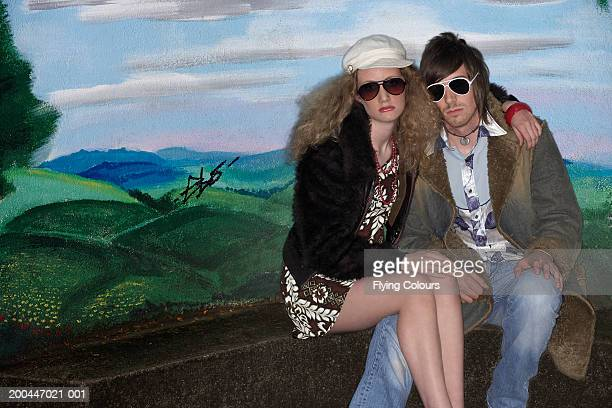 Teenage girl (15-17) and young man wearing sunglasses