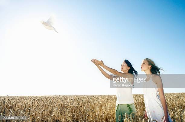 Teenage girl (13-15) and young woman releasing dove in wheat field