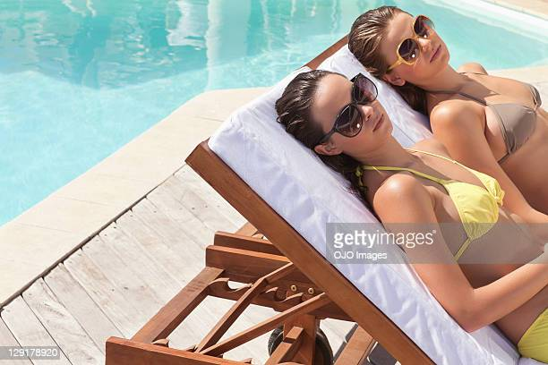 teenage girl and young woman resting on lounge chair near pool - girls sunbathing stock photos and pictures