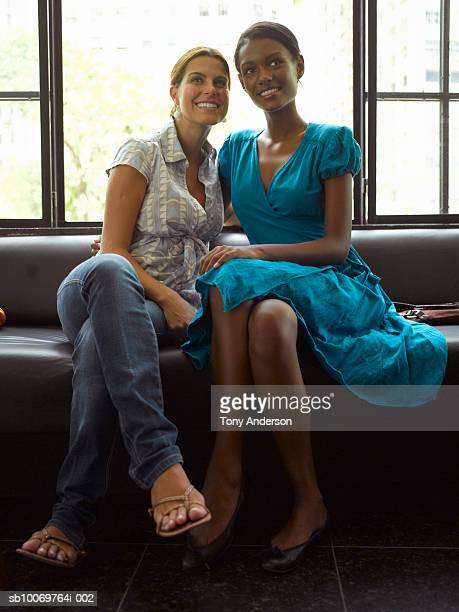 Teenage girl (16-17) and young woman sitting on sofa in restaurant, looking away, smiling