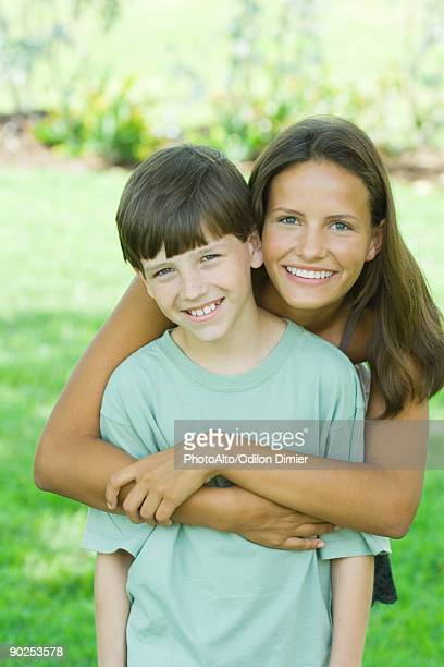 Teenage girl and younger brother smiling at camera together, portrait