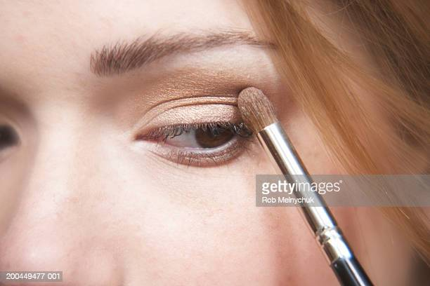 teenage girl (16-18) applying eyeshadow, close-up of eye - eye make up stock pictures, royalty-free photos & images