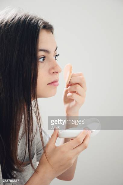 Teenage girl applying face powder
