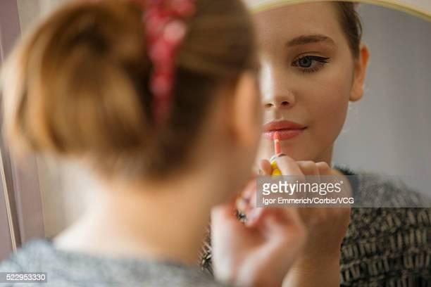 teenage girl applying lipstick in front of mirror - feminidade - fotografias e filmes do acervo