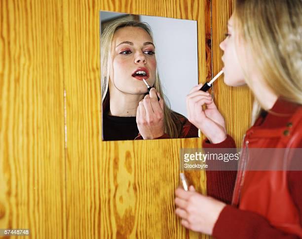 teenage girl applying lipstick in front of mirror