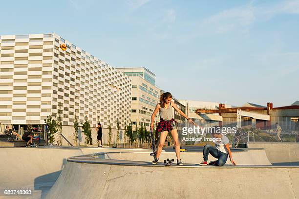 teenage girl assisting friend in getting up at skate park - ハーフパイプ ストックフォトと画像