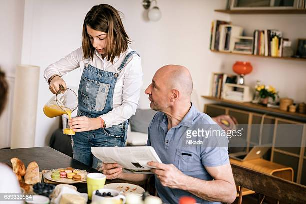 teenage girl at breakfast table serving orange juice