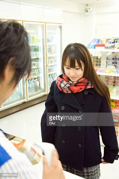 Teenage girl at checkout counter