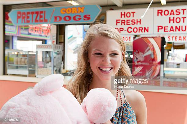Teenage girl at fun fair with teddy bear