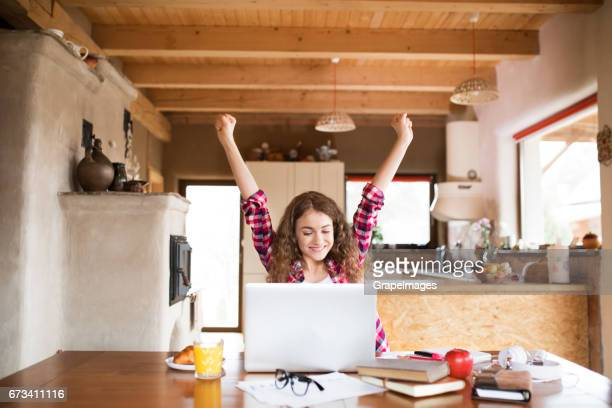 Teenage girl at home, working on notebook, studying