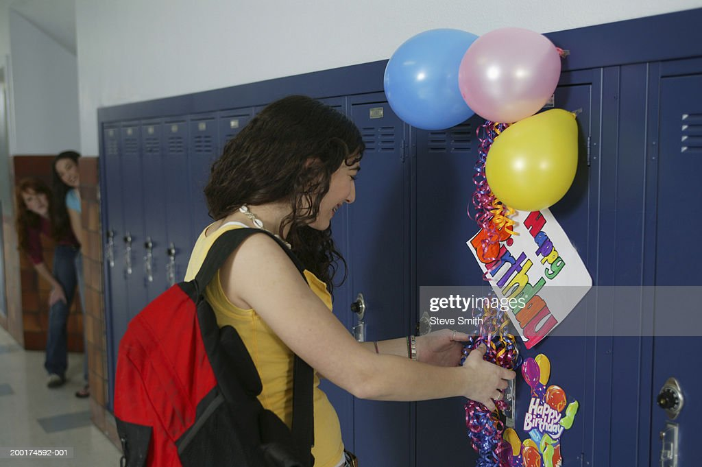 Teenage Girl At School Locker With Birthday Decorations Stock Photo