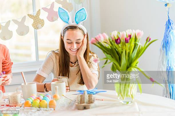Teenage girl at table reading smartphone texts whilst dyeing hard boiled eggs for Easter