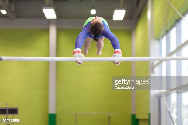 Teenage Girl Athlete Exercising on Horizontal Bar