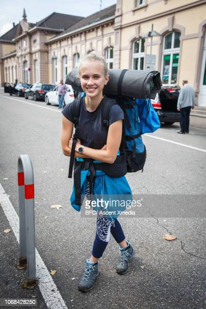 teenage girl backpacker waits on city street - rucksacktourist stock-fotos und bilder