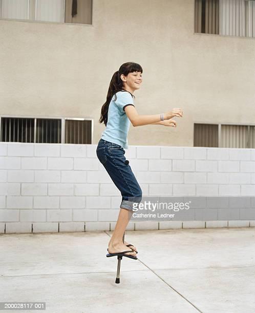 Teenage girl (13-15) balancing on pogo stick