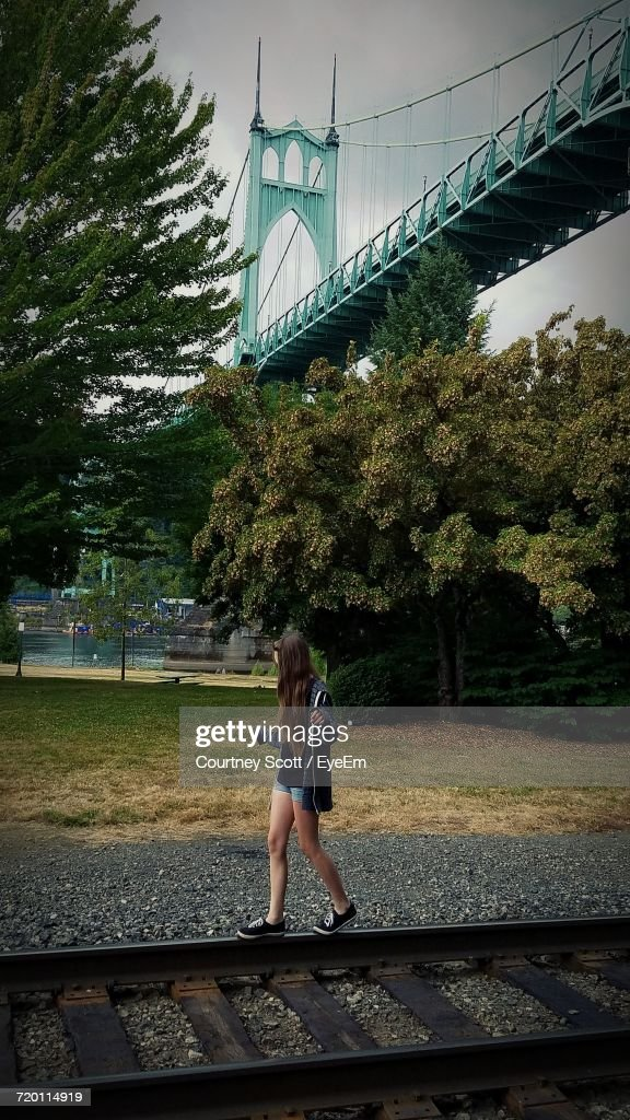 Teenage Girl Balancing On Railroad Track Against St Johns Bridge At Cathedral Park : Stock Photo