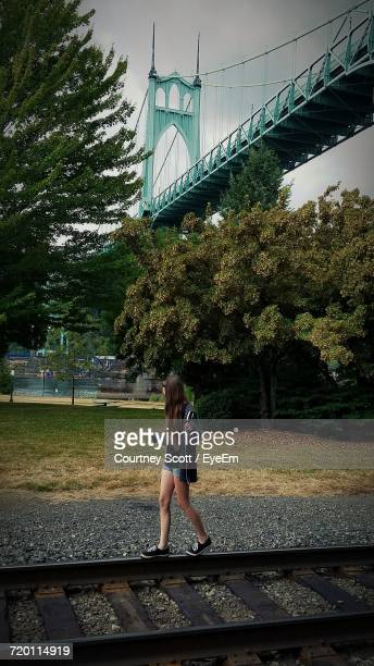 Teenage Girl Balancing On Railroad Track Against St Johns Bridge At Cathedral Park