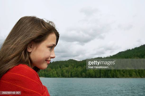 teenage girl (13-15 years) beside lake, smiling, close-up, profile - 14 15 years stock pictures, royalty-free photos & images