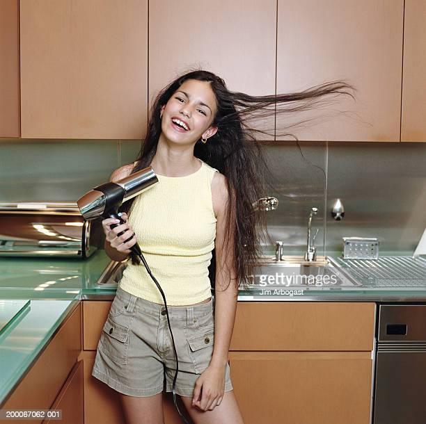 Teenage girl (12-14) blow drying hair in kitchen