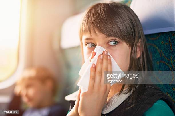 Teenage girl blowing nose on train