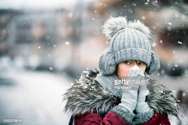 teenage girl blowing nose on winter day - winter weather stock photos and pictures