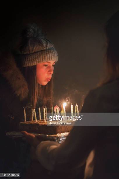 Teenage girl blowing out birthday candles