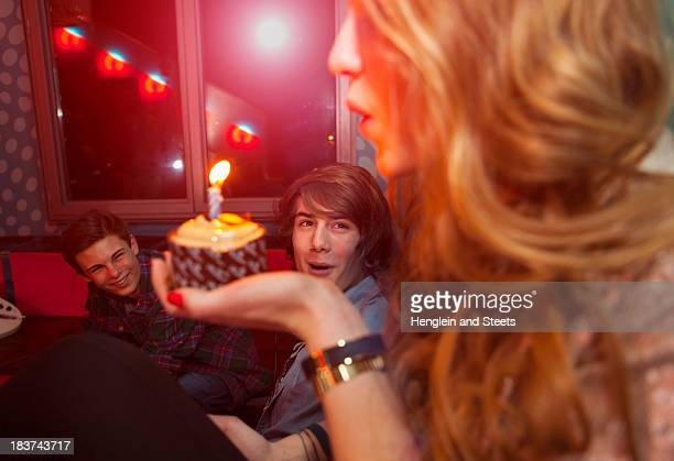 Teenage girl blowing out candle on birthday cake