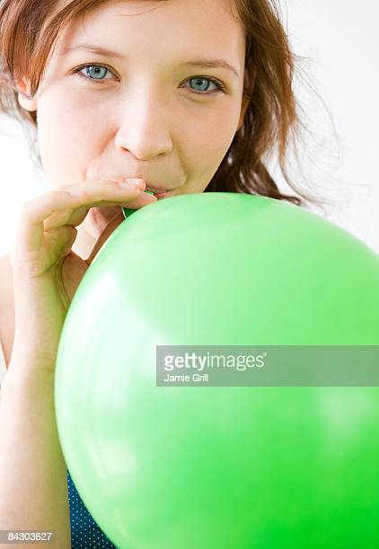Teenage girl blowing up balloon