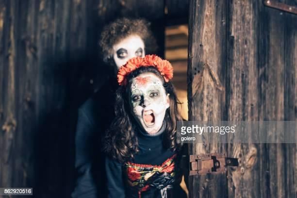 teenage girl boy in spooky halloween masks shouting
