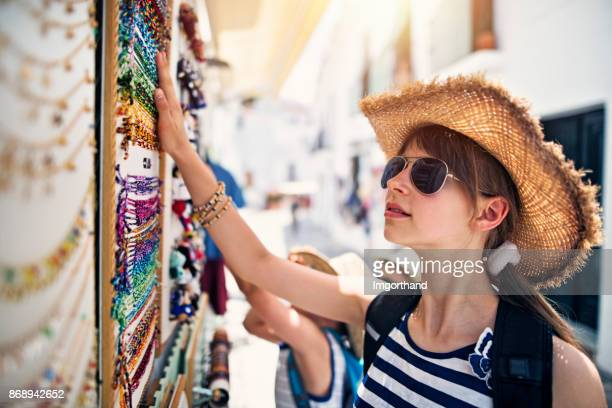 teenage girl browsing bracelets on street stand in frigiliana, andalusia, spain - souvenir stock pictures, royalty-free photos & images