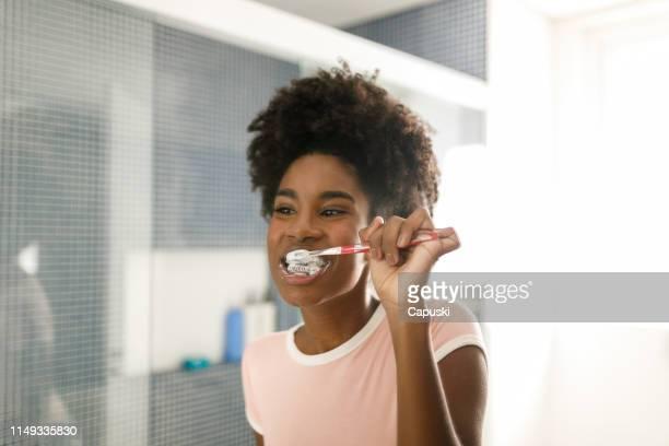 teenage girl brushing her teeth - brushing teeth stock pictures, royalty-free photos & images