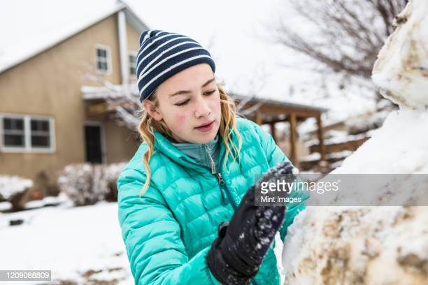 a teenage girl building a snowman - snowman stock pictures, royalty-free photos & images