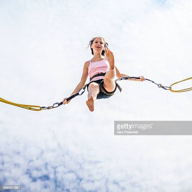 Teenage girl bungee jumping at trampoline