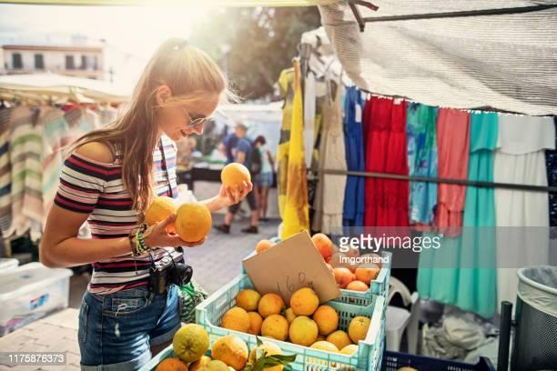 teenage girl buying fresh organic oranges at farmer's market - street market stock pictures, royalty-free photos & images