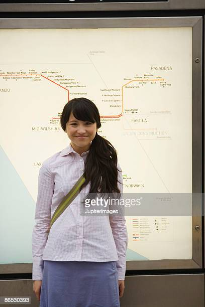 Teenage girl by a transit map
