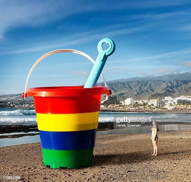 Teenage girl by an oversize beach bucket and spade