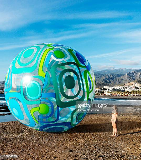 Teenage girl by an oversize inflatable beach ball