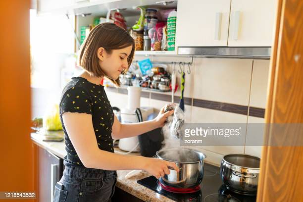 teenage girl by the stove cooking pasta in the pot - electric stove burner stock pictures, royalty-free photos & images