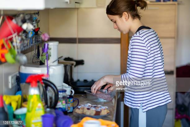 teenage girl by the stove taking meat to fry burgers - teenagers only stock pictures, royalty-free photos & images