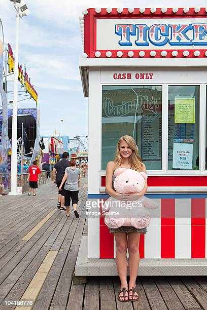 Teenage girl by ticket booth with teddy bear