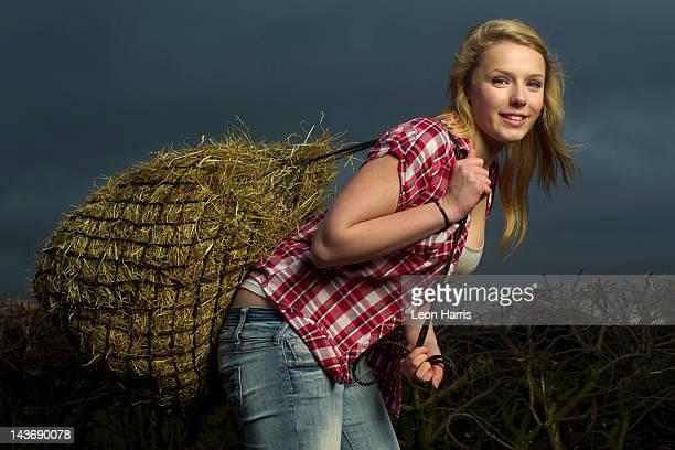 Adolescente transporte hay bales al aire libre