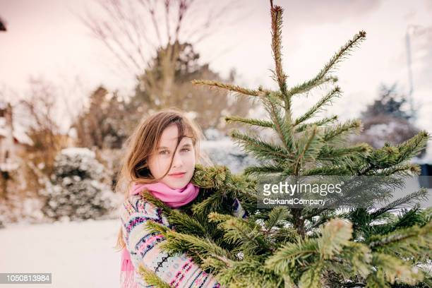 teenage girl carrying her christmas tree home. - atmosphere stock pictures, royalty-free photos & images