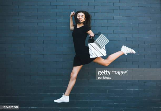 teenage girl carrying shopping bags - black dress stock pictures, royalty-free photos & images