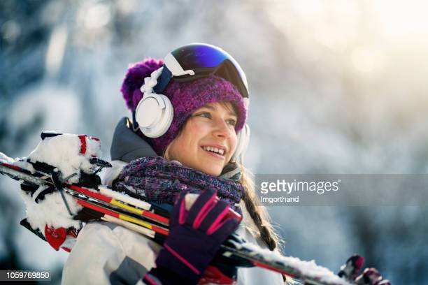 teenage girl carrying skis on a winter day - ski stock pictures, royalty-free photos & images