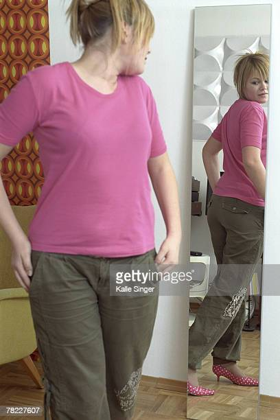 teenage girl checking her figure in the mirror - girl in mirror stock photos and pictures