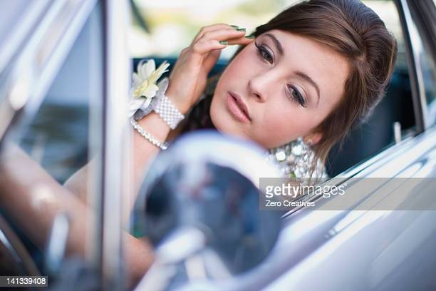 Teenage girl checking makeup in car